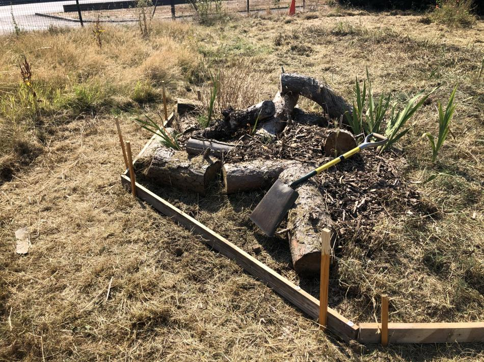 Arrange the logs around an pile or unwanted turf (laid upside down!).