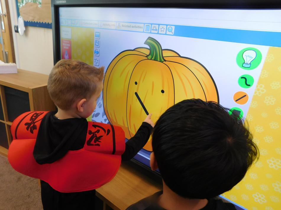 Oscar creating a face on his pumpkin.