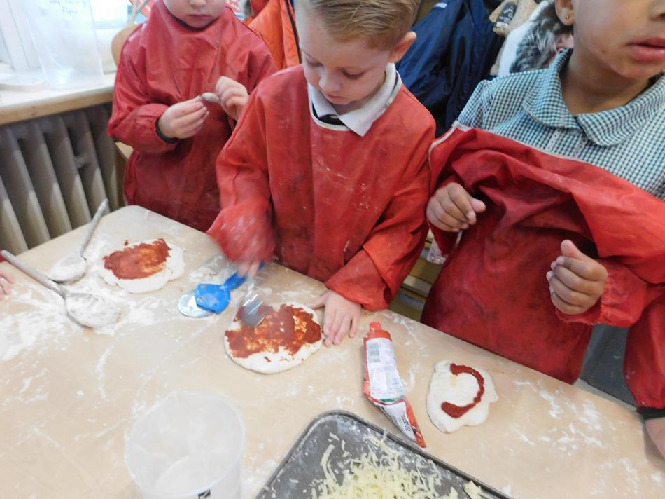 Thomas adding the tomato base for his pizza.