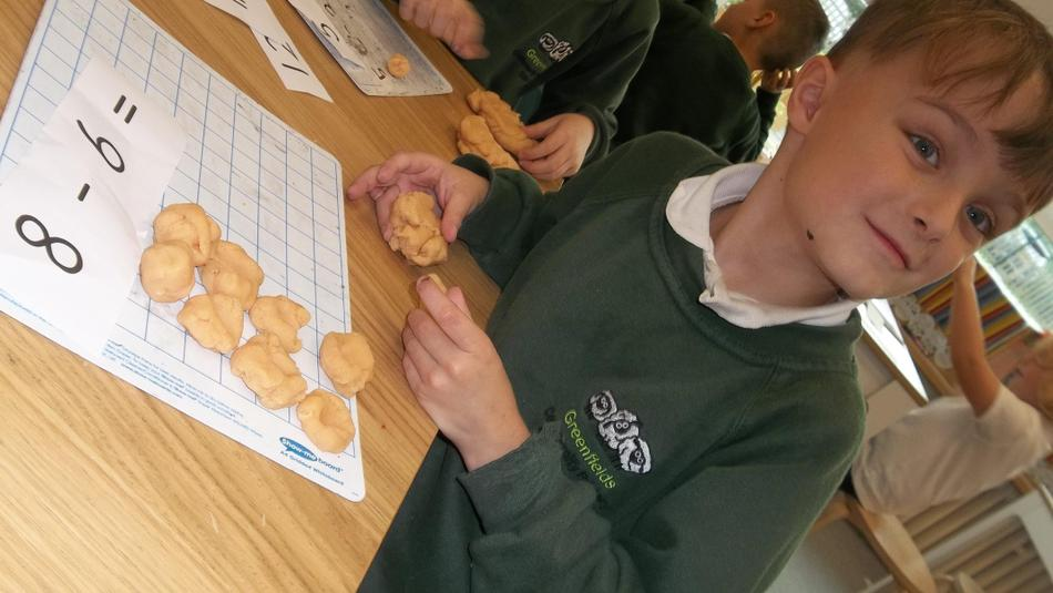 Making playdough balls and squishing the subtraction amount.