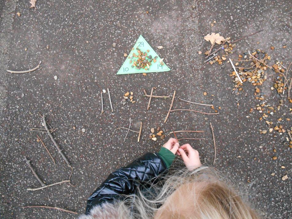 We used sticks to represent the tens and stones to represent the ones