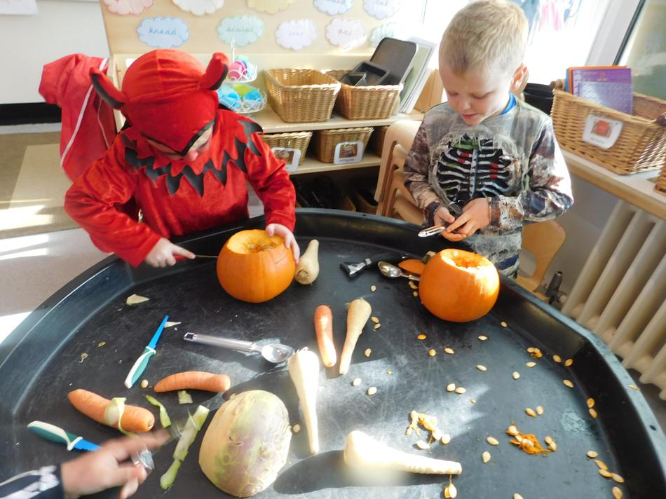 Thomas and Archie carving pumpkins.
