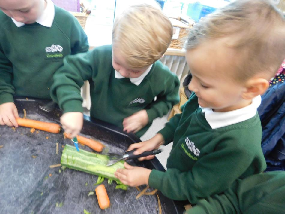 Thomas and Alfie chopping and peeling vegetables.
