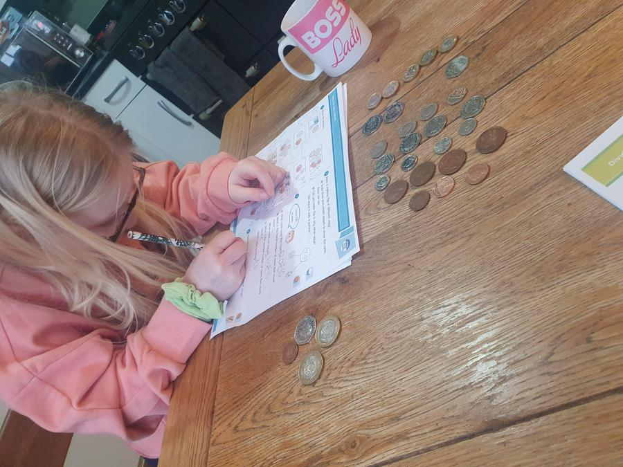 Ellie used coins complete her Maths work.