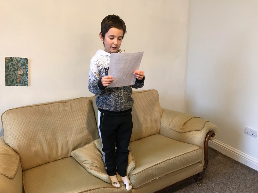 Confidently reading out his adventure story to his parents.