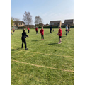 Children practicing the skills needed for rounders.