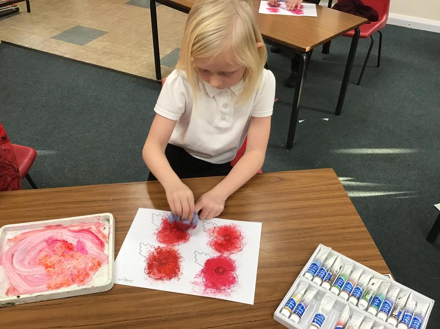 Mixing reds, orange and white watercolour to paint poppies for our class wreath.