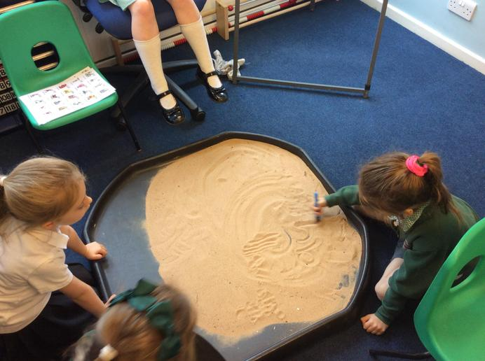 Practising letter formation in the sand