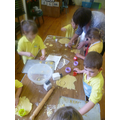Infants cooking biscuits for Macmillan Event