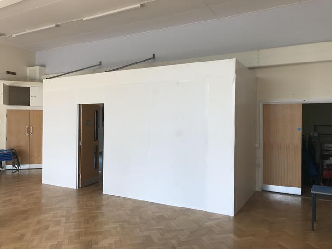 In the hall, a temporary wall is being used so that the builders can expand the kitchen