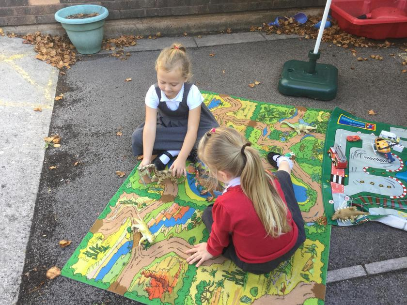 Enjoying the sunshine whilst playing with the cars.