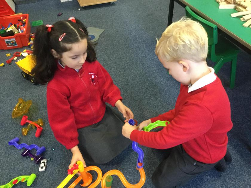 Working together to build a marble run.
