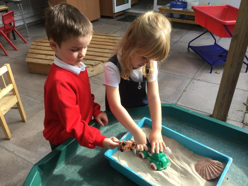 Exploring the sand and diggers in the courtyard.