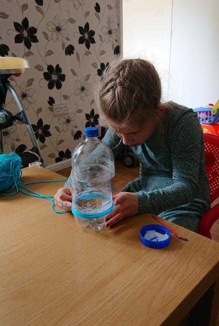 A plastic bottle, wool and glue.