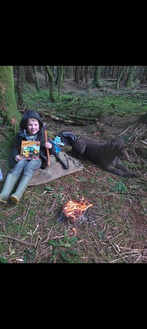 Reading his book with the campfire making a hot chocolate!