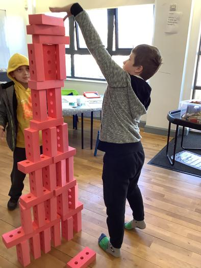 Boy making a tower out of bricks.