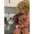 Nellie making purple playdough.