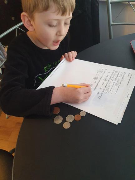 Arron using real coins to help with his maths