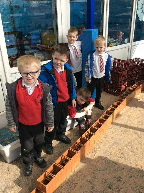 The boys made a very long brick caterpillar.