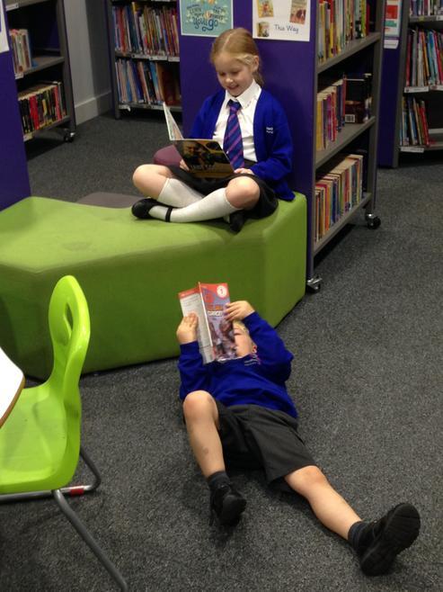 Freya and Noah enjoying books in the library.