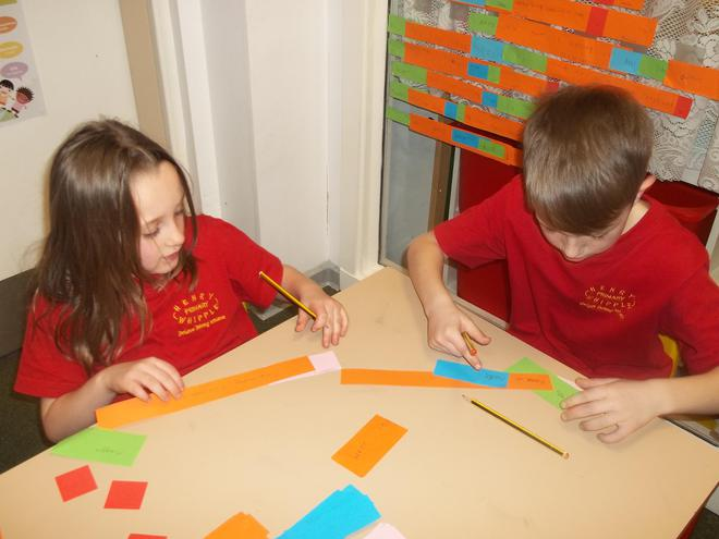 Amelia and David  from class 3 working hard writing fronted adverbial sentences using Rainbow Grammar.