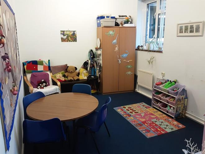 Photo shows image of small room with table, chairs, soft toys