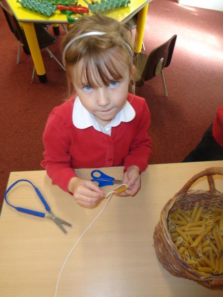 Carefully threading pasta to make necklaces