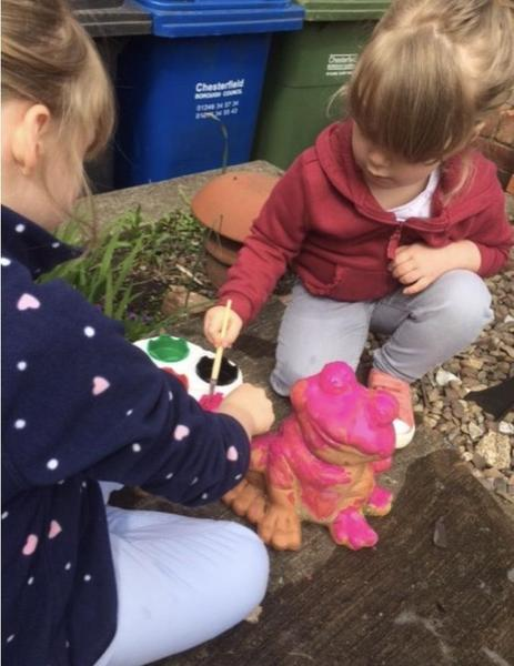 Carefully painting our garden frog! 🐸