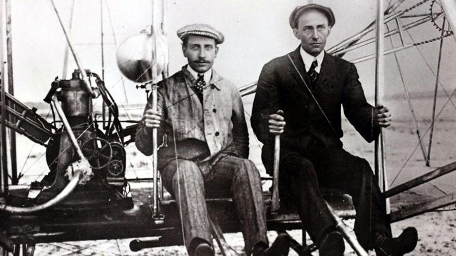 Black and white image of the Wright brothers sitting side by side on their flying machine, each holding long levers