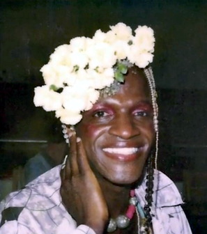 Head and shoulders photo of Martha Johnson, smiling, with a dramatic headdress of white flowers and beads.