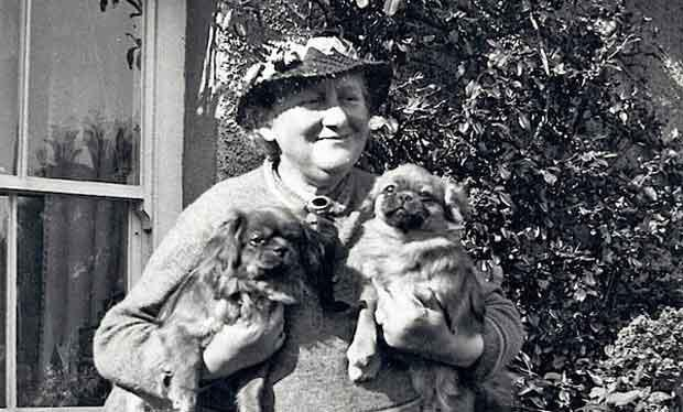 Beatrix Potter in middle age, in her garden, wearing a hat and cuddling two small dogs.