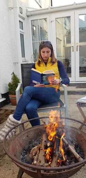 Mrs Davidson read outside by her firepit.