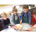 Y2 mixing up oats, apple and banana for their cookies