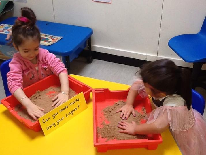 Using fingers to mark-make in sand