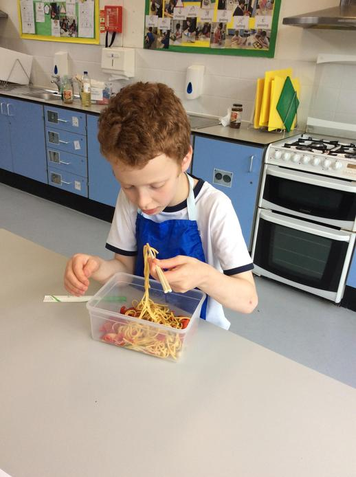 Pupil eating their noodles with chopsticks