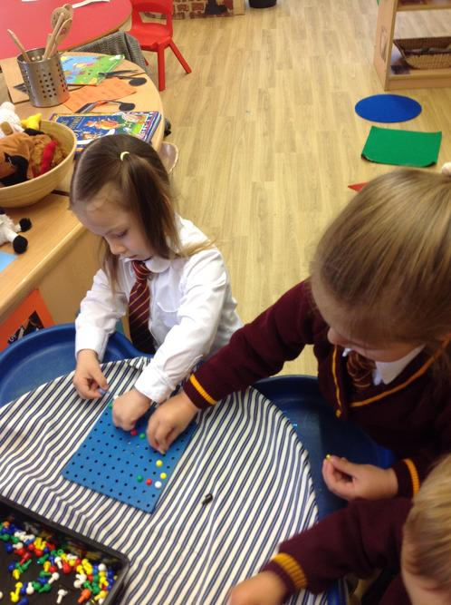 We have been trying to fill the peg boards with the pegs.