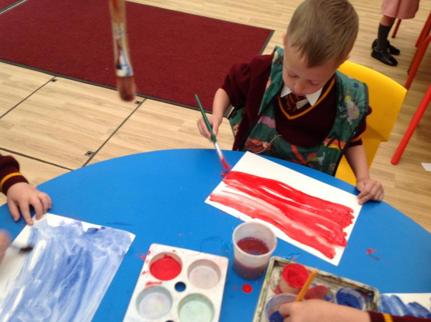 We painted backgrounds in blue and red to stick our pictures on.