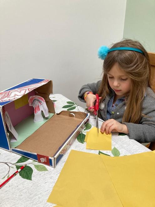 Kika making her story in a shoe box