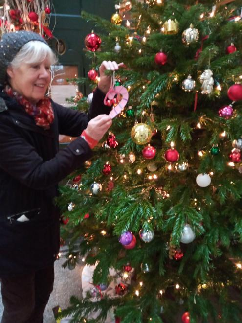 Margaret, one of the recipients, hanging up her decoration on her Christmas tree.