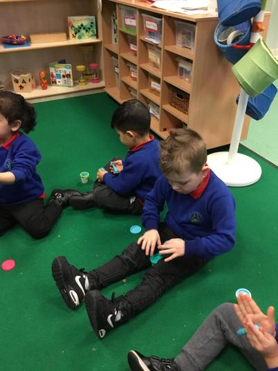 We build spacial awareness by playing with the play dough behind our backs and legs!