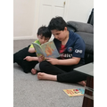 Enjoying a story with his brother.