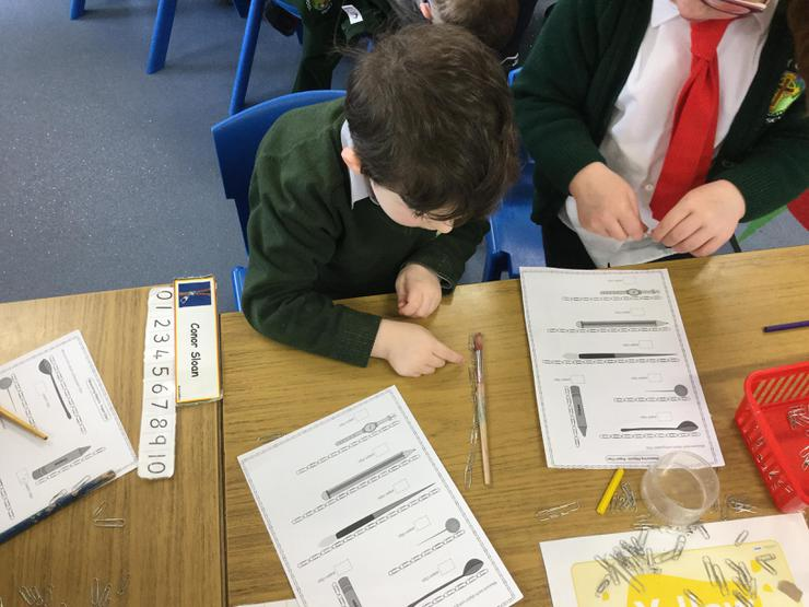 James is using paper clips to measure how long classroom objects are.