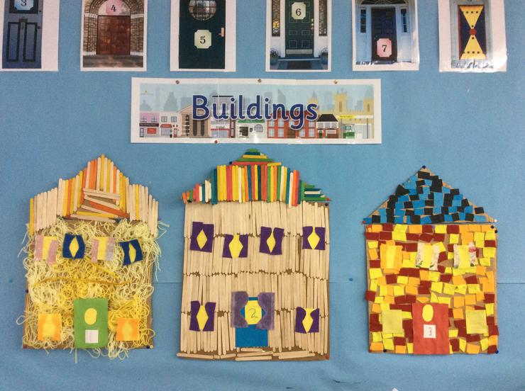 Buildings Display- We made the 3 little pigs houses using mixed media. We talked about all the shapes and patterns in the buildings, and even made curtains for the windows!