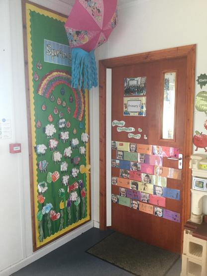 """. P1 entrance- We put together a beautiful Spring display to celebrate all the joys of Spring. We included sheep, flowers, rainbows, rain and most importantly an umbrella! On our classroom door we designed a """"building foundations"""" display. We each wrote our name in our best handwriting"""