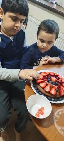 Aakarsh cake decorating with his brother.