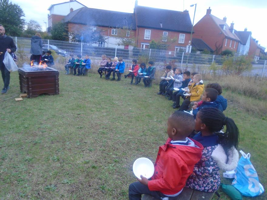 Enjoying snacks and songs around the fire!