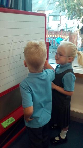 Developing small motor skills through drawing and writing on a vertical surface.