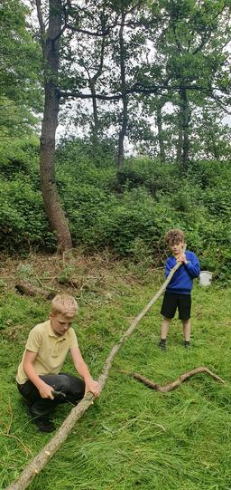 These pupils learned to work together to use a handsaw in order to cut firewood.