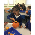 We worked together to scoop and carve a pumpkin