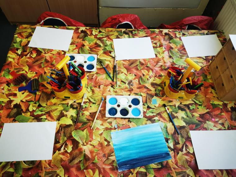 The children have been using different shades of blue to create a sea scene.